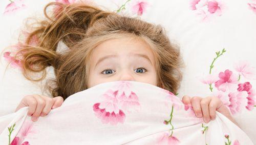 Das Bild zeigt ein Mädchen im Bett, das sich erschreckt.