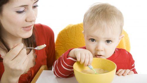 Das Bild zeigt eine Frau, die ein Kleinkind füttert.