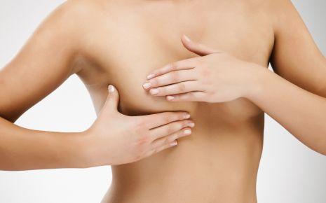 Brustuntersuchung: Man sieht eine Frau, die ihre Brust abtastet.