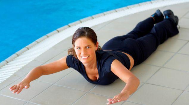 Eine Frau liegt am Rand eines Schwimmbeckens und macht eine Fitnessübung.