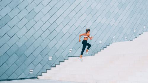 Eine Frau rennt eine Treppe hoch.