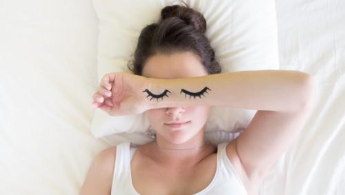 Junge Frau schläft und hat gemalte Augen auf dem Unterarm