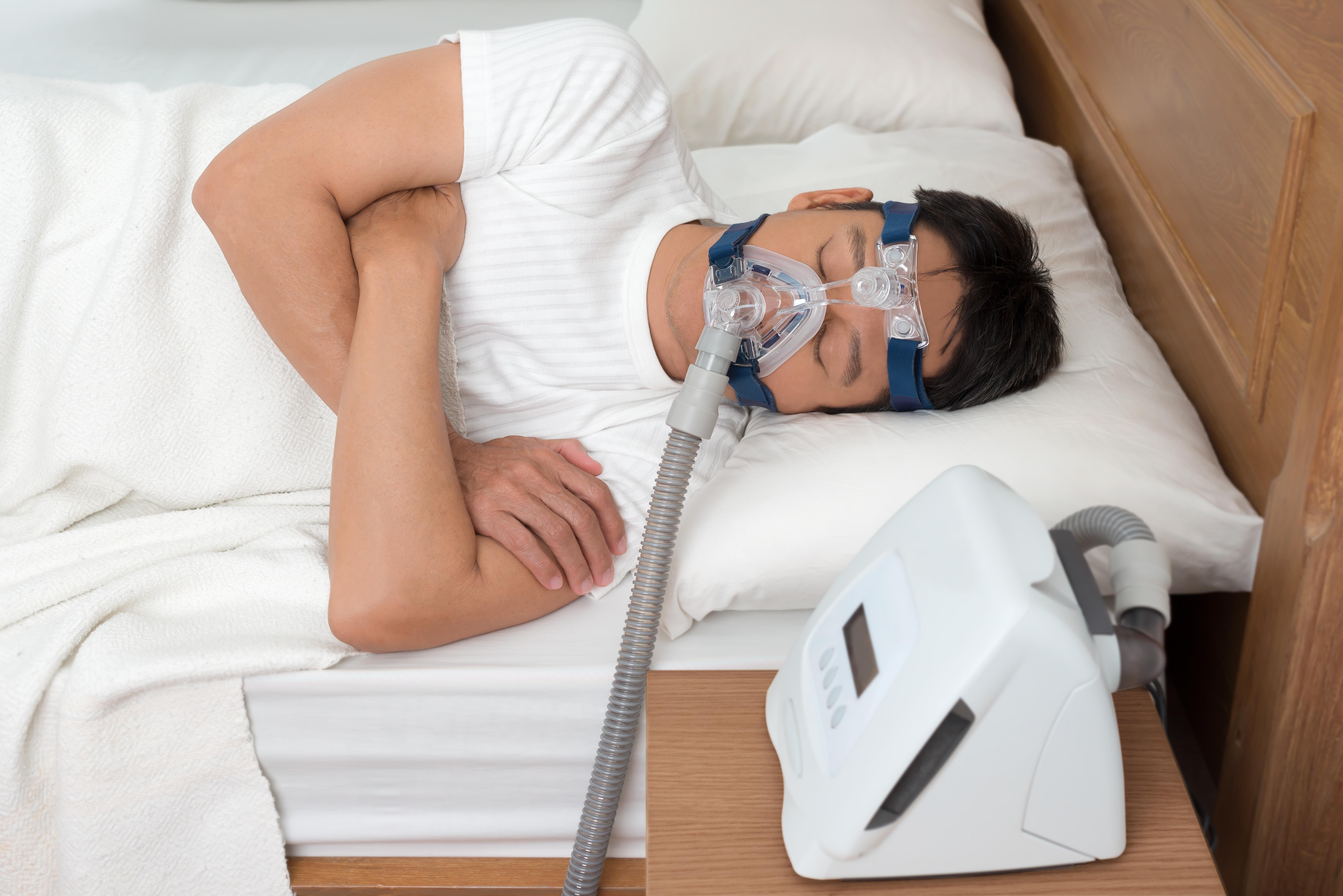 Ein Mann schläft mit einem Atemgerät.