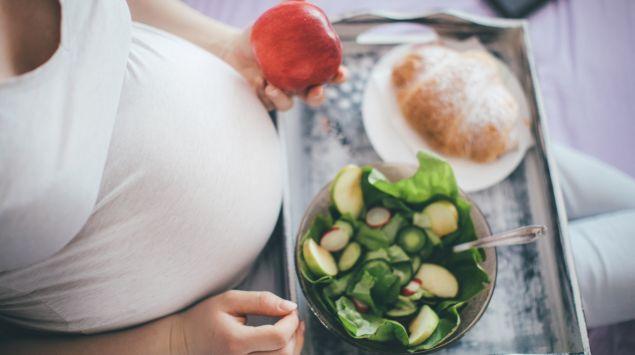 Eine Schwangere sitzt mit einem Essenstablett auf dem Schoß auf dem Bett.