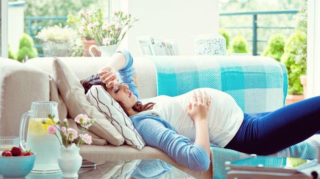 Eine Schwangere erschöpft auf der Couch.