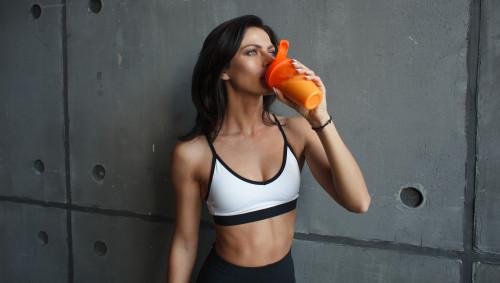 Eine Frau trinkt einen Proteinshake beim Sport.
