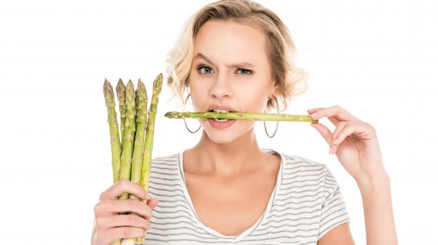 Eine Frau beißt in eine Stange grünen Spargel und schaut skeptisch