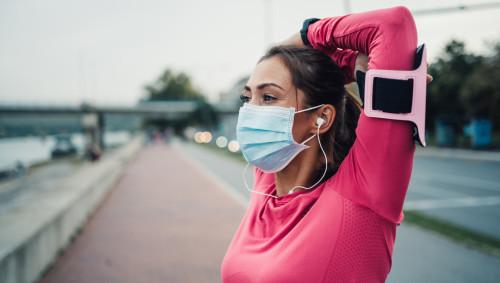 Eine Frau mit Mund-Nasen-Maske dehnt sich nach dem Laufen.