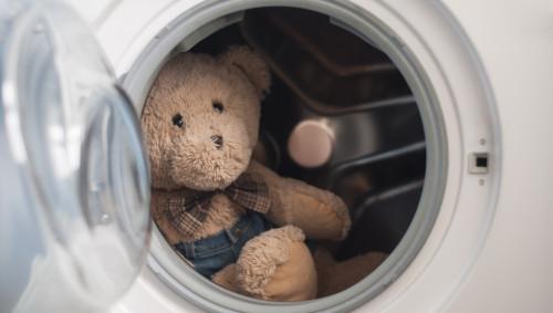 Ein Teddybär sitzt in einer Waschmaschine.