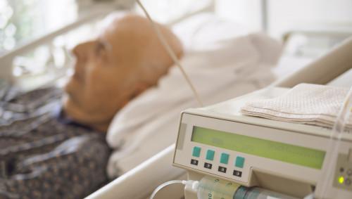 Ein alter Mann liegt im Krankenhausbett