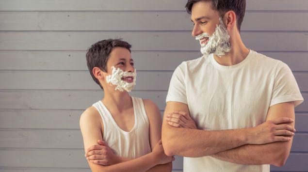 Vater und Sohn mit Rasierschaum im Gesicht.