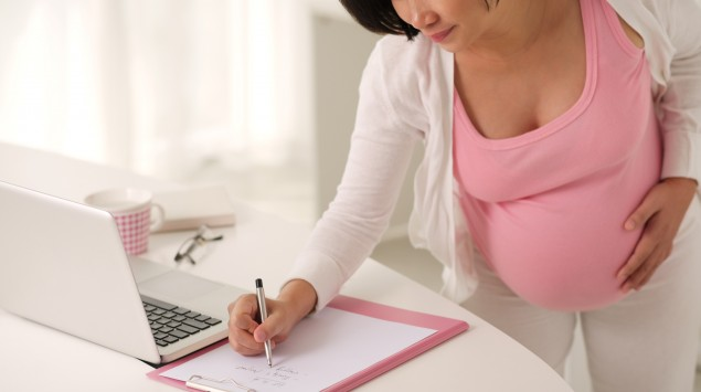 Schwangere notiert Wichtiges auf einer Liste.