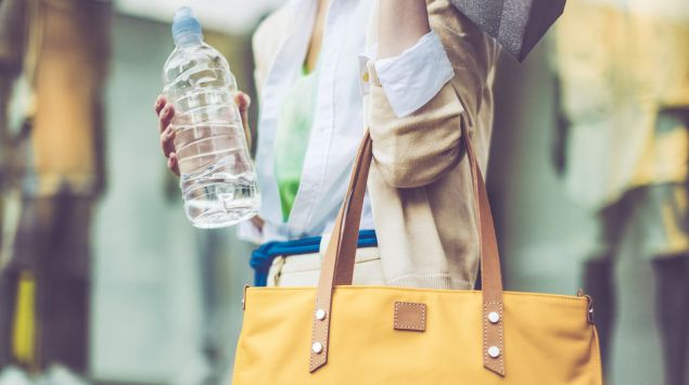 Das Bild zeigt eine Frau mit Handtasche und Wasserflasche.