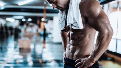 Das Bild zeigt einen jungen Mann mit Handtuch im Fitnessstudio.