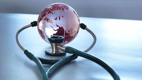 Man sieht eine Weltkugel aus Glas und ein Stethoskop.