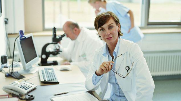 Eine Ärztin am Schreibtisch, im Hintergrund weitere Ärzte.